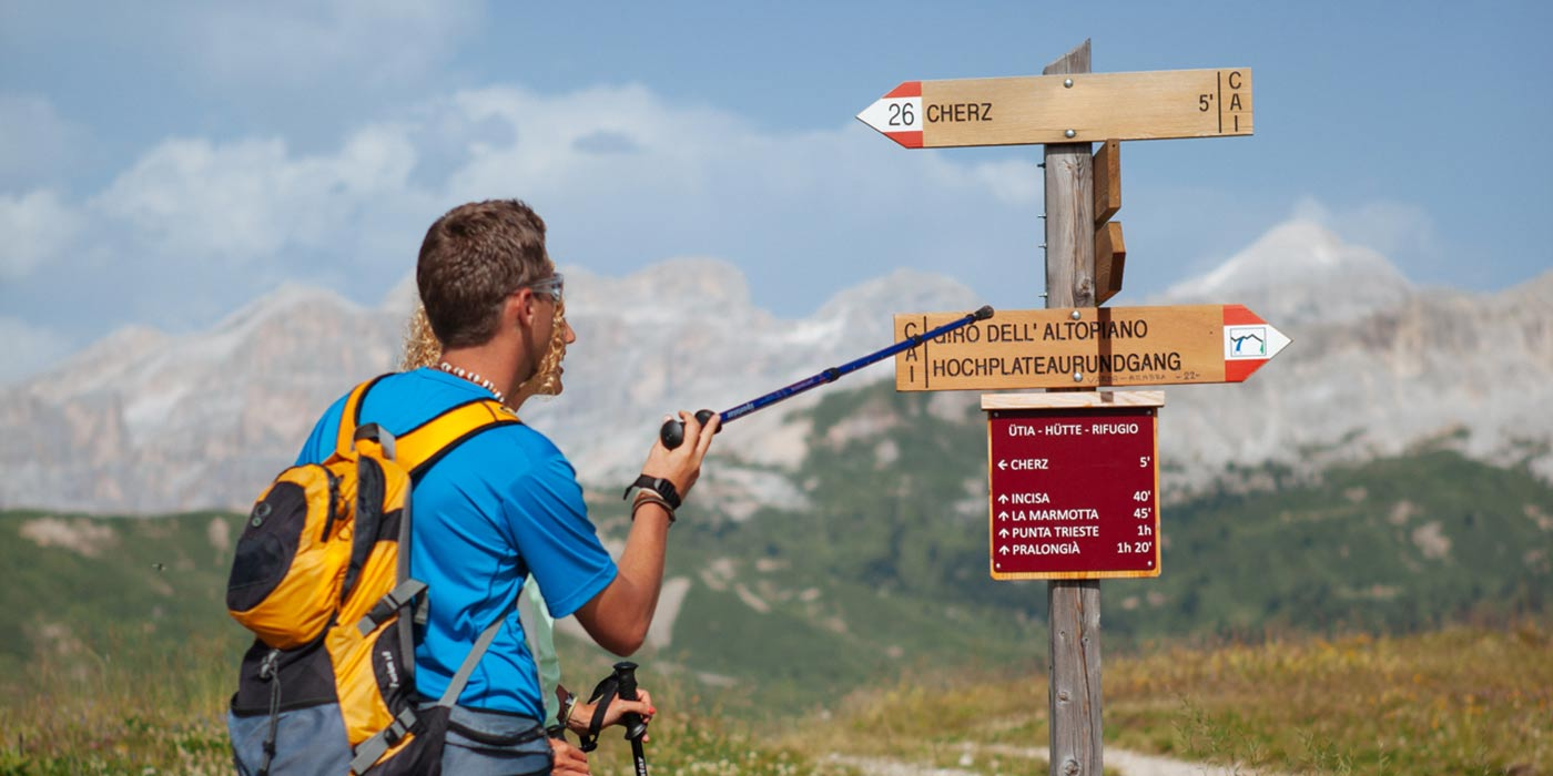 Couple of hikers reads the wood trail signs with the Dolomites on the background