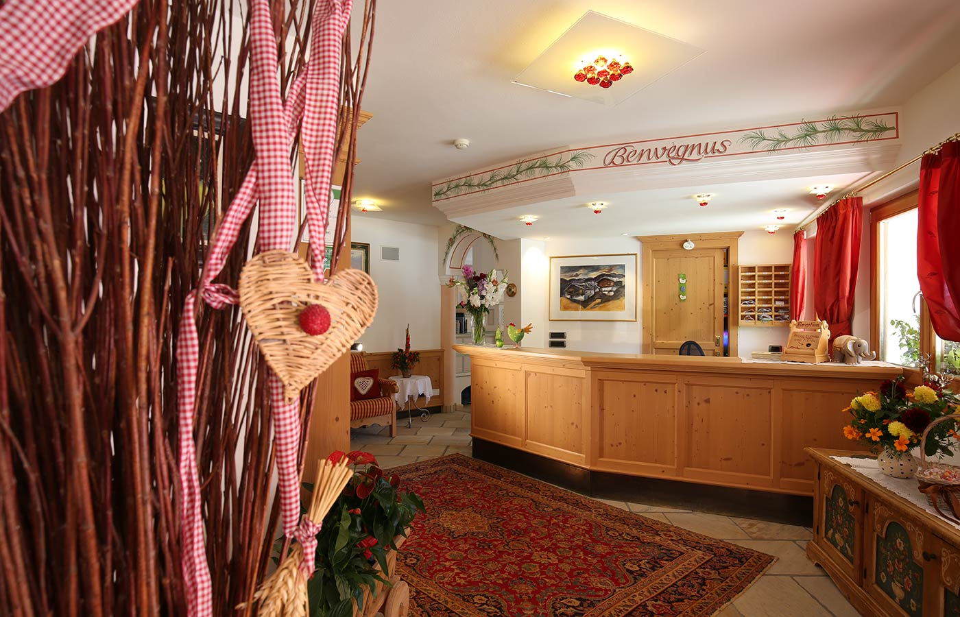 Hotel Mesdìs reception with wood furnishings, flowers on the desk and a carpet on the floor