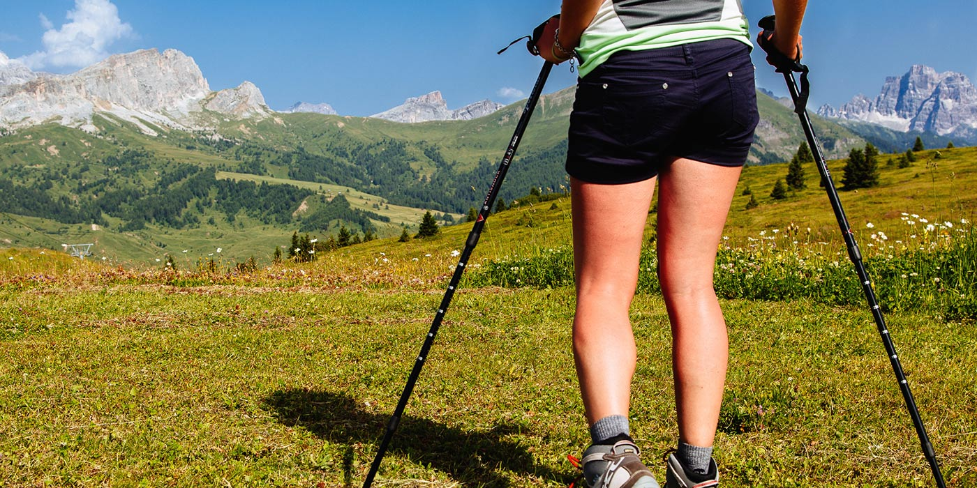 Girl trekking with the sticks on a mountain meadow with the Dolomites on the background