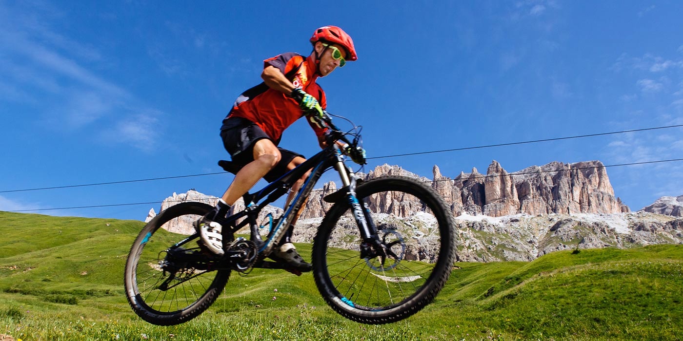 Man in mountain bike on a green meadow with the Dolomites on the background