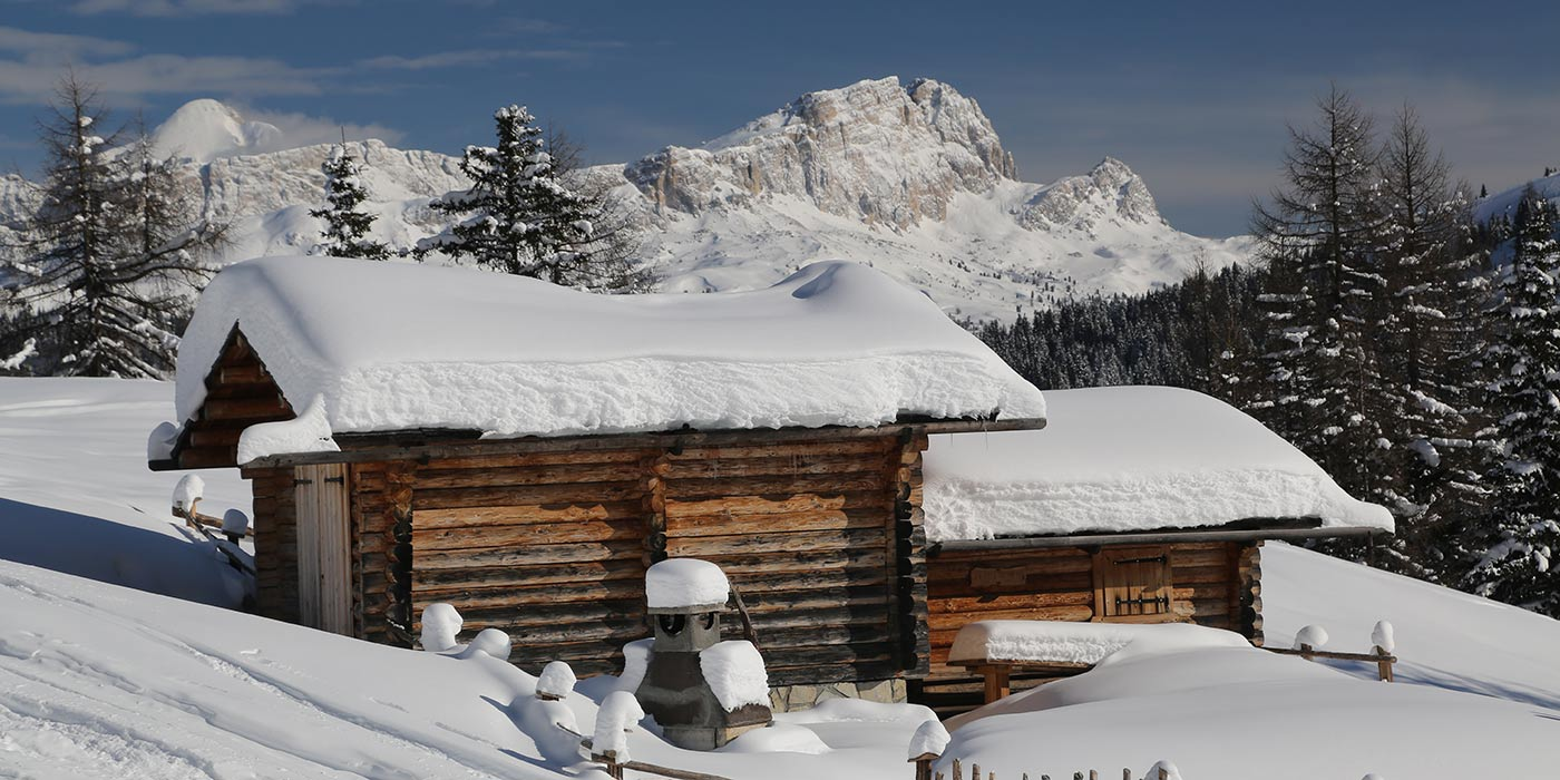 Wood hut in winter covered with snow with the snow Dolomites on the background