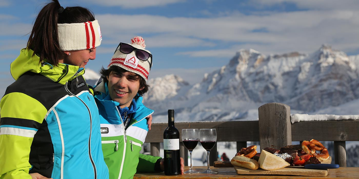 Couple in a winter suit has a sneck with wine and traditional food with the Dolomites on the background
