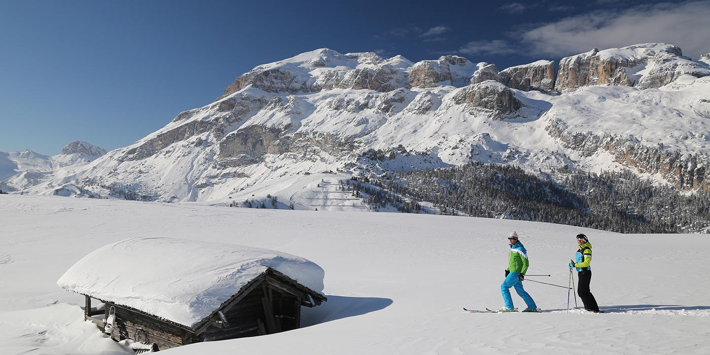 Couple of skiers near a snow hut with the Dolomites' landscape on the background