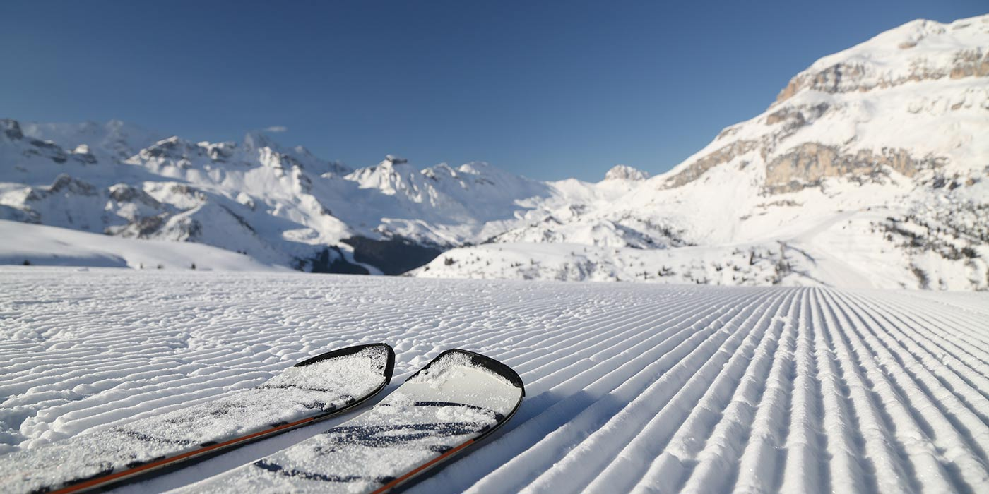 A couple of ski on a snow track with the Dolomites on the background