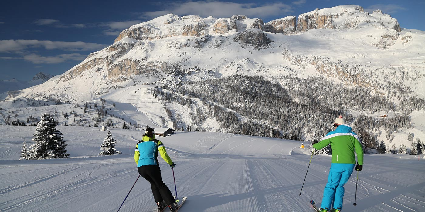 Couple of skiers on a snow track with the Dolomites on the background