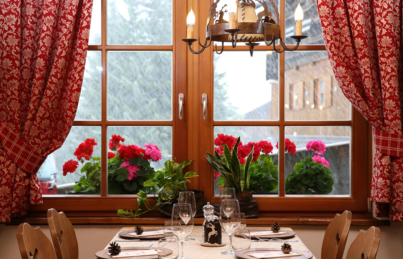 Wood window with red curtains and flowers on the sill over a prepared table