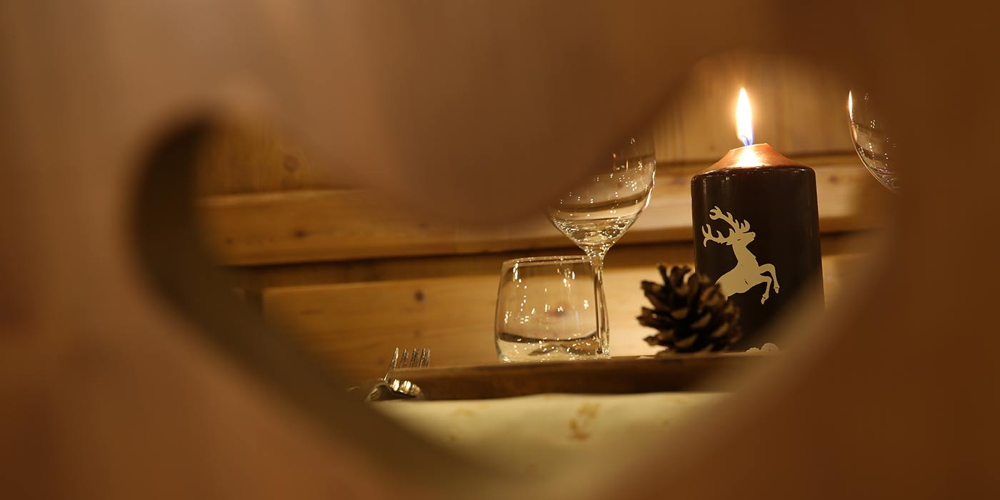 Prepared table with lit candle as seen through a wood chair's back