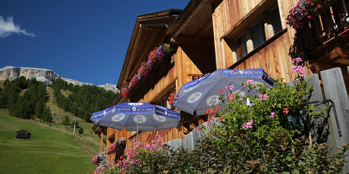 Hotel Mesdì in summer with umbrellas and flowers on the foreground and the Dolomites on the background