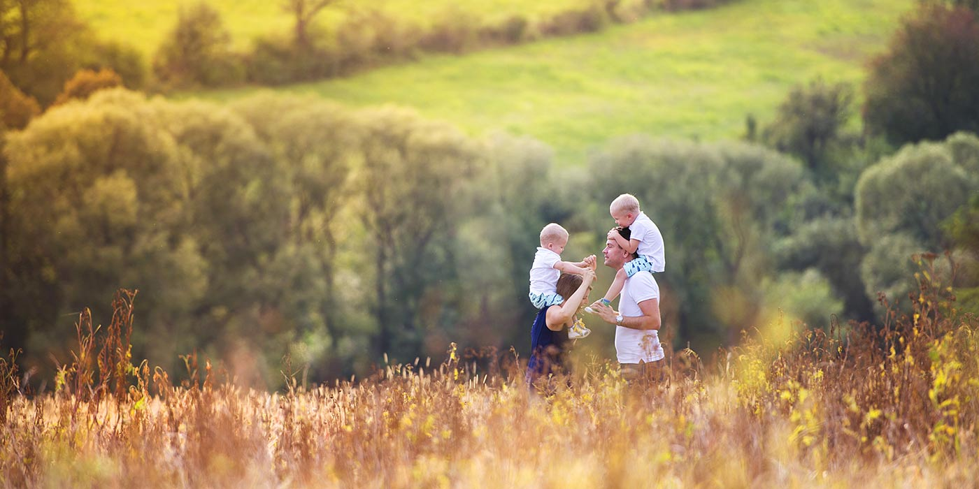 Family in an autumn meadow with green meadows and trees on the background