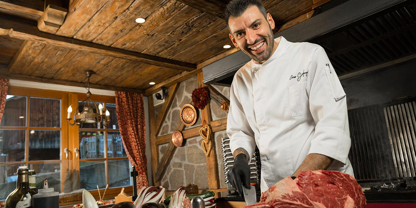 Mesdì's chef in the kitchen smiling while slicing a ham