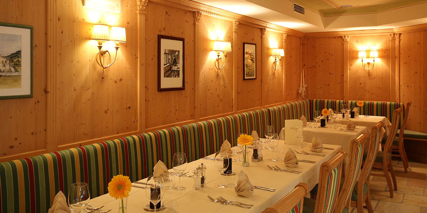 Hotel Mesdì's lunch room with wood walls, prepared tables and colores pillows
