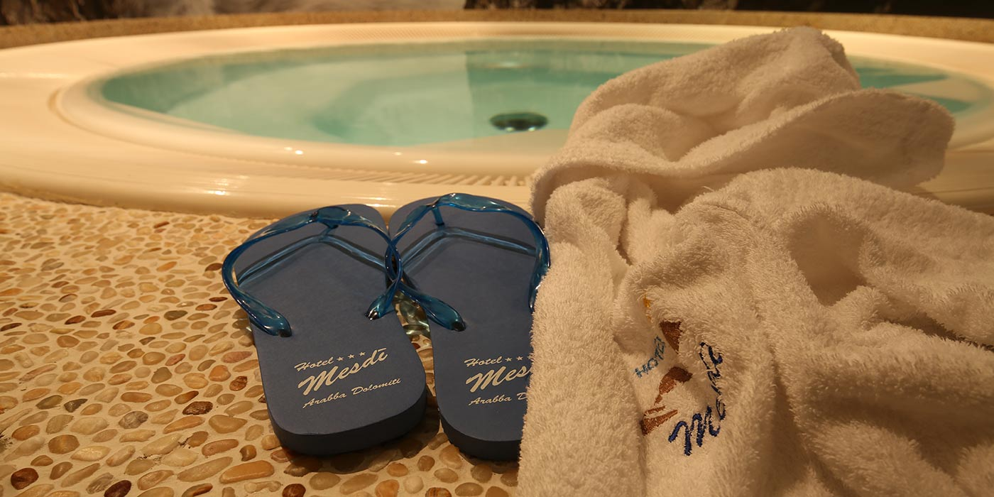 A couple of black slippers and a white bathrobe on the side of Hotel Mesdì's whirlpool