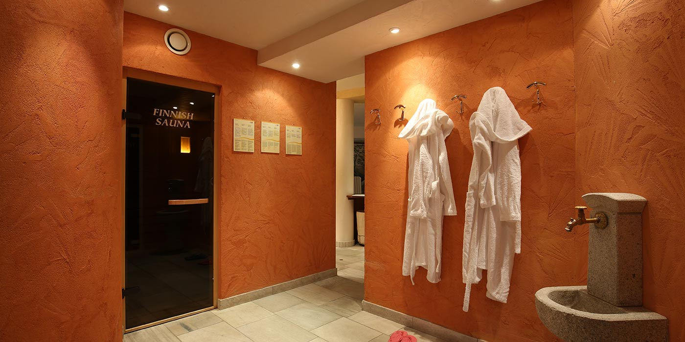 The entrance of Hotel Mesdì's finnish sauna with stone fountain and bathrobes hanging on the wall