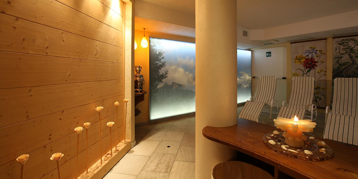 Hotel Mesdì's wellness area decorated with wood with a lit candle and sunbeds at the wall