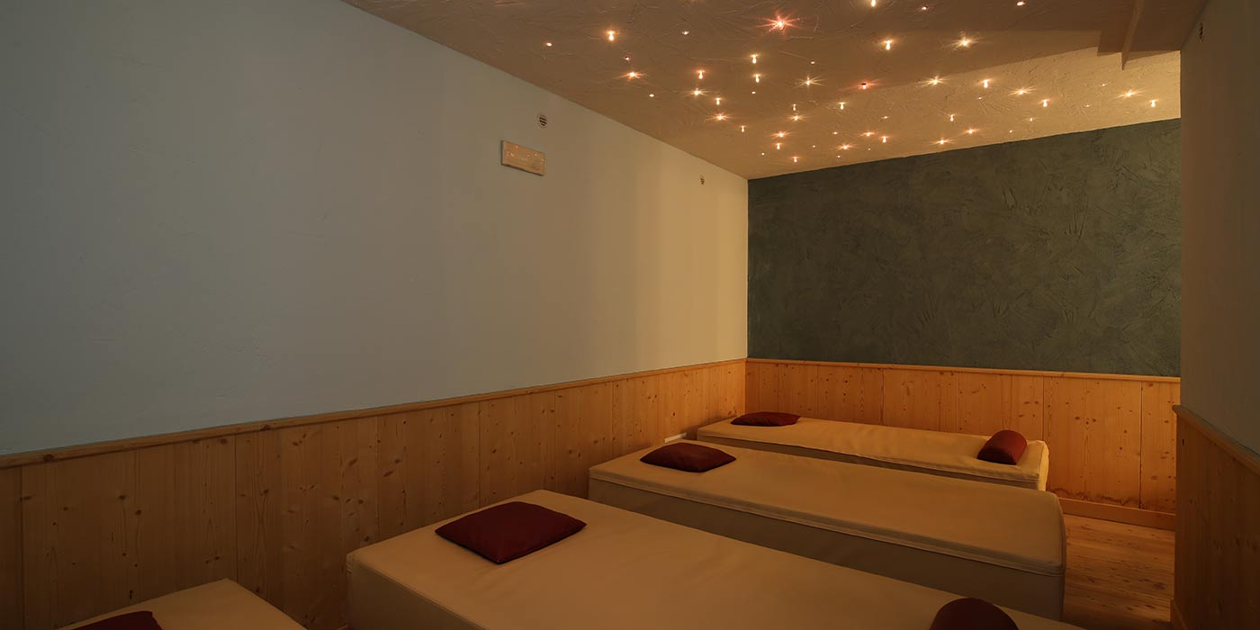 Hotel Mesdì's relax area with white sunbeds and colored lights on the ceiling